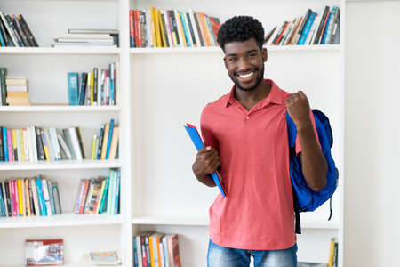 Cheering afro american male student with backpack and copy space
