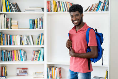 Laughing afro american male student with backpack and copy space