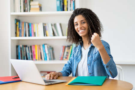 Successful latin female student with curly hair at computer