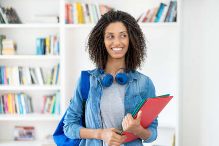 Laughing latin female student with curly hair and paperwork