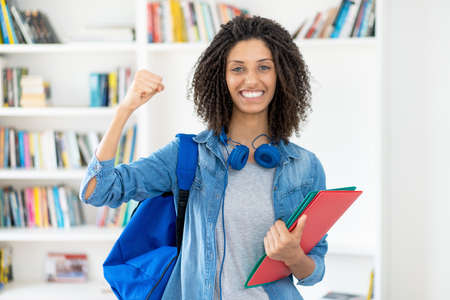 Cheering latin female student with curly hair and paperwork