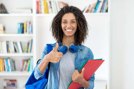 Successful latin female student with curly hair and paperwork