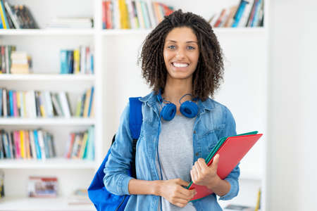 Pretty latin female student with curly hair and paperwork