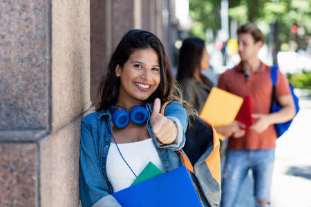 Successful laughing female student showing thumb up with friends in background in front of university building Banco de Imagens