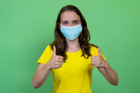 British young adult woman recommending face mask against covid-19 infection