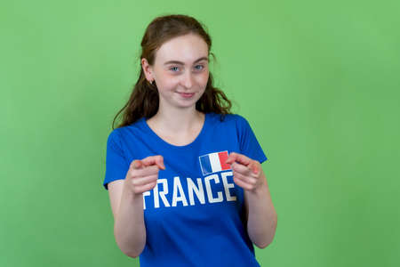 Happy french female soccer supporter isolated on green background