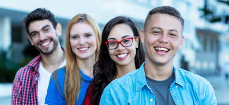 Laughing german young adult man with group of friends in line