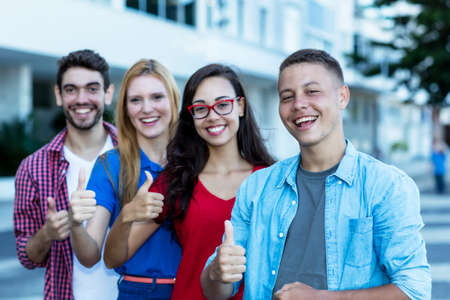German young adult man with international friends in line showing thumb up