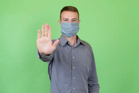 Man wearing protective mask as protection against coronavirus pandemic covid-19 and gesturing stop