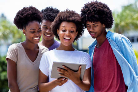 Happy african american young adults streaming movie with digital tablet outdoor in summer in city