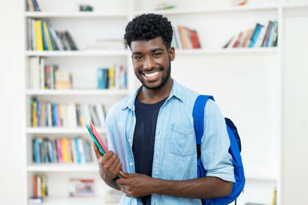 Laughing young african american male student with beard at library of university