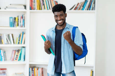 Successful young african american male student with beard at library of university