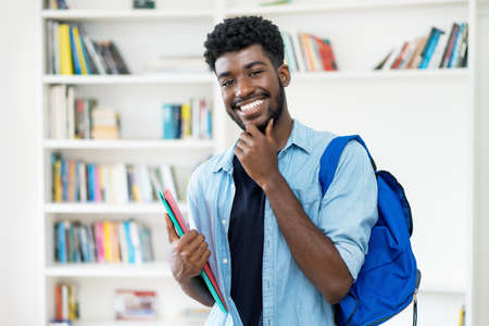 Smart young african american male student with beard at library of university