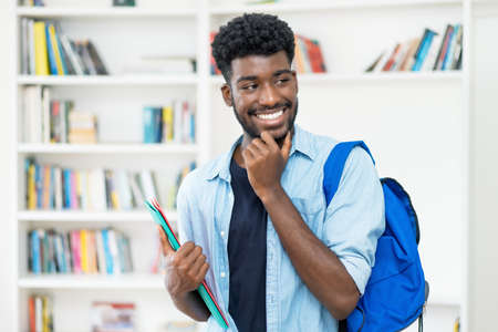Handsome young african american male student with beard at library of university