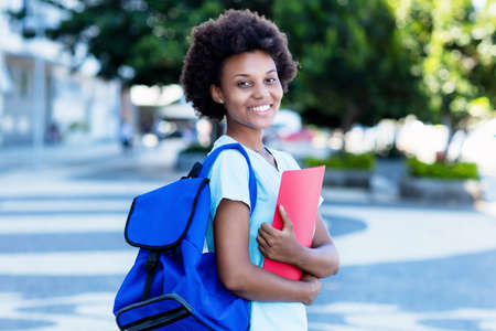 Laughing african american female student in city walking to university