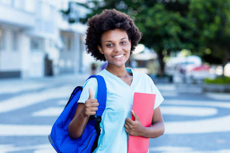 Motivated african american female student showing thumb up
