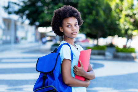 Young african american female student in city walking to university