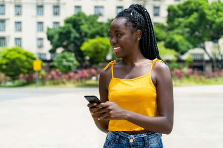 Pretty african american girl with phone sending message