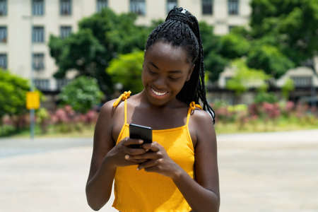 Beautiful african american girl with phone sending message