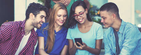 Laughing influencer girl with mobile phone and group of young adult friends in vintage retro look