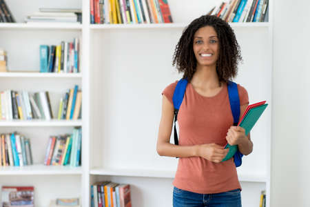 Young female student with curly hair and copy space indoors at the library 免版税图像