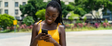 Happy african american girl with phone sending message outdoor in summer in city