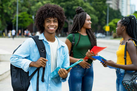 Handsome afro american male student with group of young adults