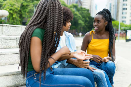 Group of african american male and female young adults in discussion outdoor in city in summer 免版税图像