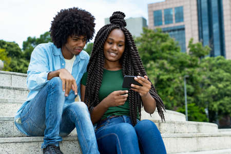 Young african american male and female influencer posting message with mobile phone outdoor in city in summer