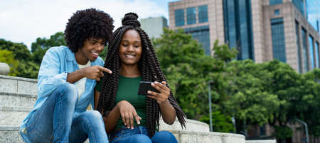 African american male and female influencer posting message with mobile phone outdoor in city in summer