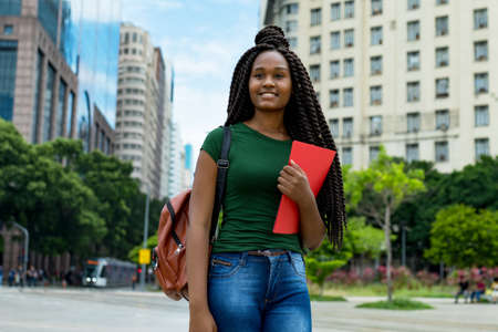 Beautiful african american young adult female student with braids outdoor in city in summer 免版税图像