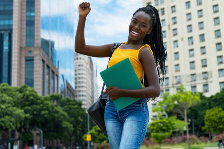 Successful cheering afro american female student with braids and backpack outdoor in city in summer 免版税图像