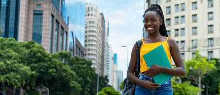 Pretty afro american female student with braids and backpack outdoor in city in summer