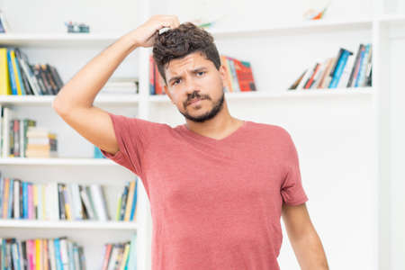 Confused mexican mature adult man with beard indoors at home Standard-Bild