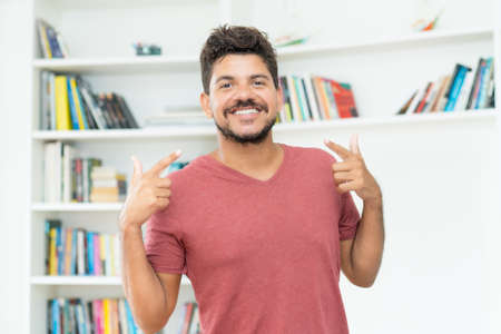 Cheerful mature adult mexican man with beard indoors at home