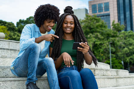 Laughing african american male and female influencer posting message with mobile phone outdoor in city in summer