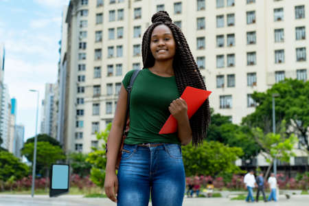 Laughing african american young adult female student with braids outdoor in city in summer 免版税图像 - 164190984