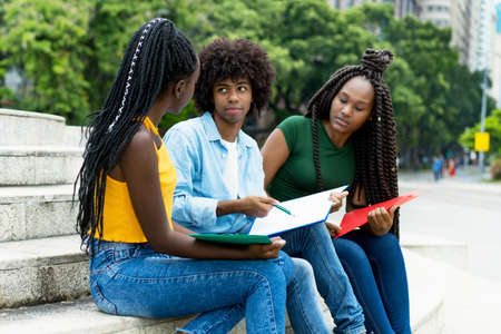 African american male and female students talking about homework of university outdoor in summer in city 免版税图像 - 164190991