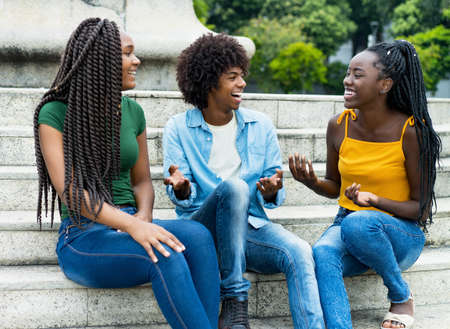 Laughing group of african american female and male young adults outdoor in summer in city 免版税图像 - 164190992