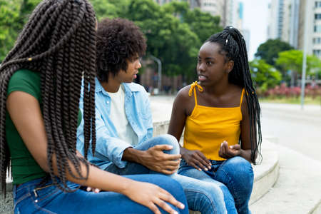 Talking group of african american female and male young adults outdoor in summer in city
