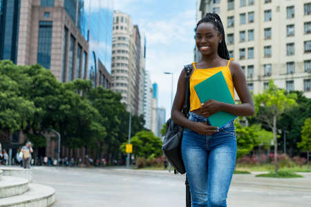 Laughing afro american female student with braids and backpack outdoor in city in summer 免版税图像 - 163968807