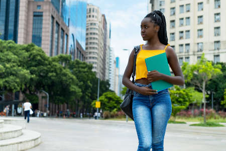 Thinking afro american female student with braids and backpack outdoor in city in summer 免版税图像 - 164191003