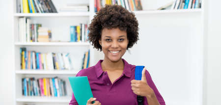 Successful afro american female student with backpack and paperwork at classroom of university 免版税图像 - 165335028