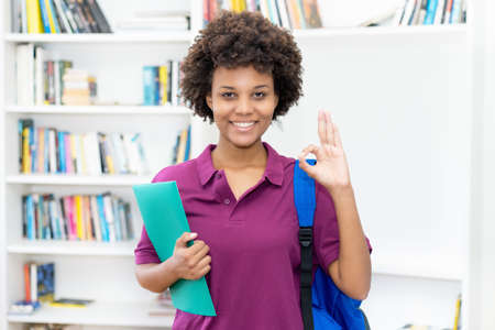 Beautiful afro american female student with backpack and paperwork at classroom of university 免版税图像 - 165477713