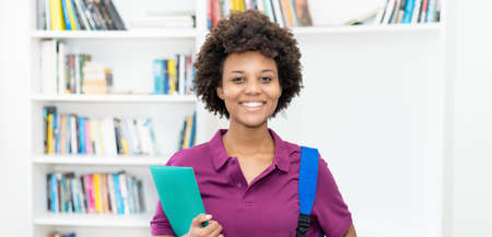 Laughing afro american female student with backpack and paperwork at classroom of university 免版税图像 - 165477714