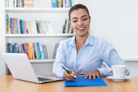 Laughing latin american business trainee with paperwork at desk at office 免版税图像 - 165486734