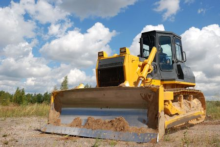 Bulldozer is stnading in the field against the blue sky and clouds background