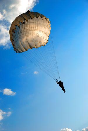 single parachute jumper against blue sky background photo