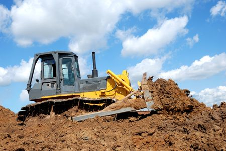 brigt: Bulldozer moving ground over brigt sky outdoors