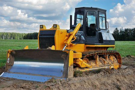 excavate: bulldozer standing outdoor in green field